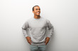 African american man on white wall background posing with arms at hip and laughing