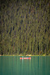 Banff, Canada - Sept 15th 2017 - Couple of tourists doing kayak in a green water lake with pine trees in the background at the Banff National Park in Canada