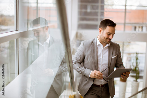 Leinwanddruck Bild Happy businessman dressed in suit standing  in modern office  and using tablet