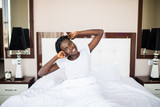 Lets start new day. Beautiful young African woman in tank top lying in bed and stretching her arms - 236768803