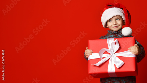fototapeta na ścianę Smiling funny child in Santa red hat holding Christmas gift in hand. Christmas concept.