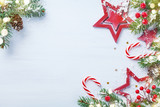 Merry Christmas holiday card or banner with snowy fir branches, red stars and festive decorations. Magic bokeh lights.