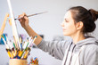 Girl artist paints a picture on canvas with brushes - 236795040