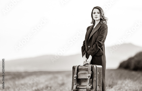Portrait of young woman in red coar at autumn countryside with suitcase. Image in black and white color style © Masson