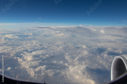 View from the airplane porthole. Blue sky in the horizon and white clouds below. Jet engine aircraft. - 236809444