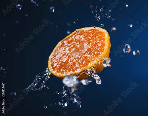 Half of a juicy Mandarin in the spray of water - 236825667