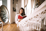 Beautiful dark-haired girl dressed in pants and sweater reads a book lying in a hammock next to the round mirror on the floorin a cozy decorated room with a New Year tree - 236835097