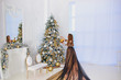 Young beautiful woman with long hair in a dress with a train decorates the Christmas tree