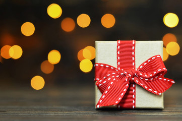 Christmas gift with red ribbon and blurred Christmas lights in background