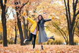 Pretty woman and teen girl are posing with bunch of maple's leaves in autumn park. Beautiful landscape at fall season. - 236842829