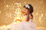 girl child is playing with christmas lights, yellow background, pink dress - 236843033