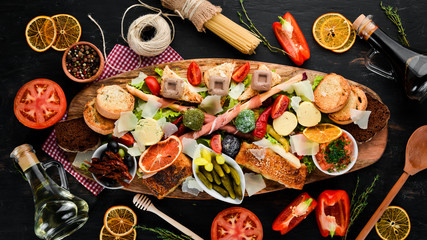 A set of food. Snacks of Italian cuisine. On a wooden background. Top view. Free copy space