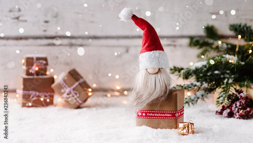 Frohe Weihnachten - Kleiner Weihnachtswichtel sitzt auf einem Geschenk und freut sich auf Heiligabend - 236843243