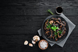 Fried mushrooms with parsley on the plate. On a black background. Top view. Free space for your text.