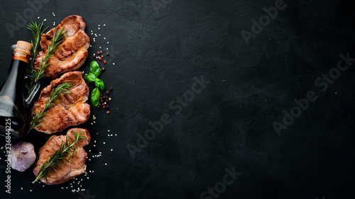 Meat steaks with rosemary. Grill, barbecue. On a black stone background. Top view. Free copy space. - 236844225