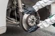 Leinwandbild Motiv Brake disk with worker's hands in gloves close up