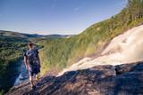 Person steht an Wasserfall und genießt weite Aussicht über die Landschaft