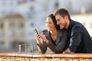 Happy couple using phone in a balcony at sunset