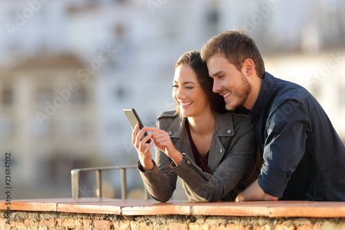 Happy couple using phone in a balcony at sunset - 236847012