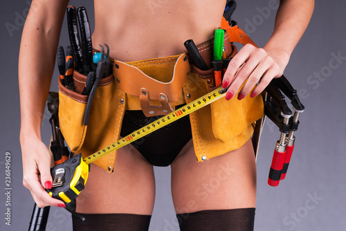 Leinwandbild Motiv Working tools lie in a leather belt, dressed on a beautiful female body. Girl in black bikini.