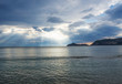 Leinwanddruck Bild - mediterranean sea and sky with dramatic clouds with sun rays beams and view on porto timony bay hills, sunset hour, Corfu, Greece