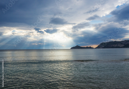 Leinwanddruck Bild mediterranean sea and sky with dramatic clouds with sun rays beams and view on porto timony bay hills, sunset hour, Corfu, Greece