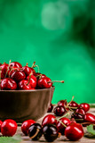 Sweet cherries in a plate on a wooden table