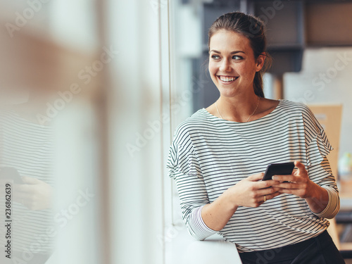 Woman looking out of a window standing in office