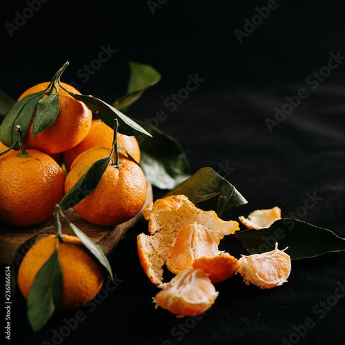 Dojrzałe mandarynki z liśćmi na czarnym tle
