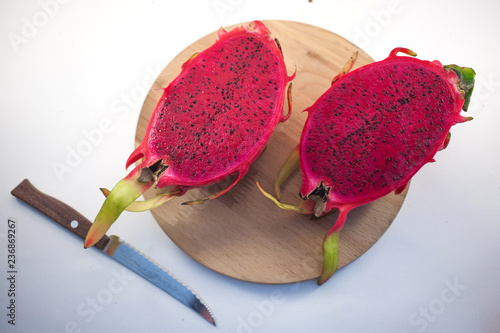 Exotic ripe pink Pitaya or Dragon fruit. Red Pitahaya tropical fruit cut in half on wood with a knife