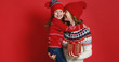 Leinwanddruck Bild - happy family mother and child daughter with christmas gifts on red background