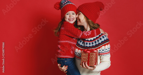 Leinwanddruck Bild happy family mother and child daughter with christmas gifts on red background