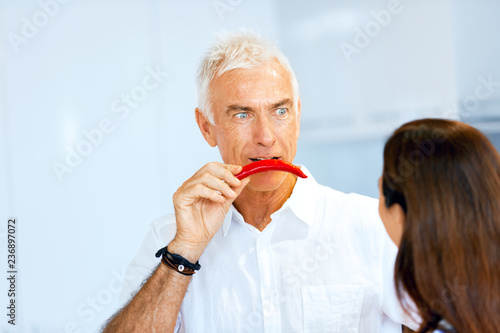 Man holding a red pepper next to his face