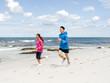Leinwandbild Motiv Young Couple Running along sea shore