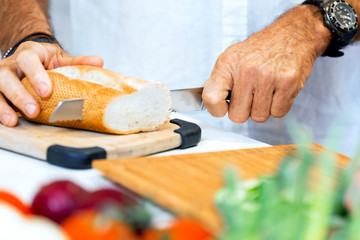 Male hands cutting bread