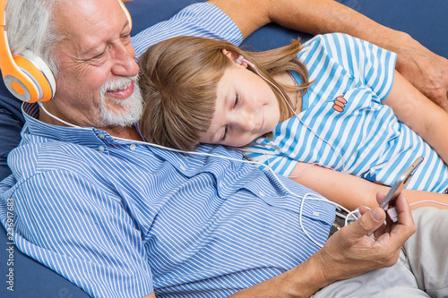 grandfather and grandson with headphones listen to music hugging each other on the couch  - 236917683