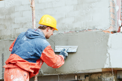 facade work. builder plastering outside wall with putty knife float © Kadmy