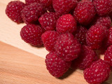 Pile of raspberries on natural wooden background. Close up.