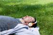 Leinwandbild Motiv Relaxing on spring grass with music over headphones.