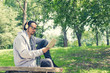 Smiling man reading book and listening music in the park.