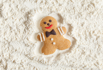 Funny gingerbread man lies in flour