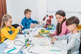 attentive schoolchildren working on robot at STEM robotics lesson - 236938836