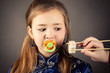 attractive young girl with pacifier in mouth looking sushi rolls
