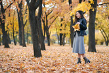 Pretty woman is posing with bunch of maple's leaves in autumn park. Beautiful landscape at fall season. - 236943204
