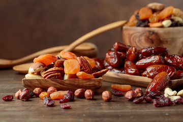 Various dried fruits and nuts in wooden dish.