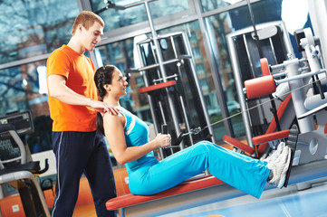 Personal training in gym. fitness instructor exercising woman with training simulator