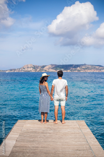 Leinwandbild Motiv Back view of young couple in love relax on pier in Italy, woman looking to camera