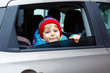 Leinwandbild Motiv Portrait of pretty toddler boy sitting in car seat. Child transportation safety. Cute healthy kid boy looking happy about family vacations with car through window during standing in traffic jam