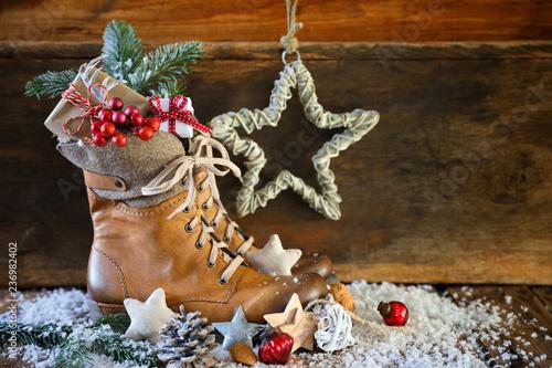 Leinwanddruck Bild Nikolaus  -  Lederstiefel mit Geschenken vor Holz Hintergrund