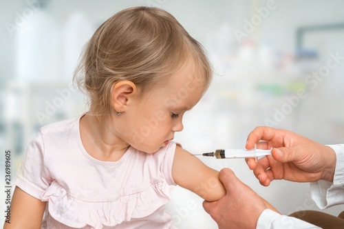 Leinwandbild Motiv Pediatrician doctor is injecting vaccine to shoulder of baby